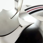 Detalj av silverkanna med handtag av plexiglas